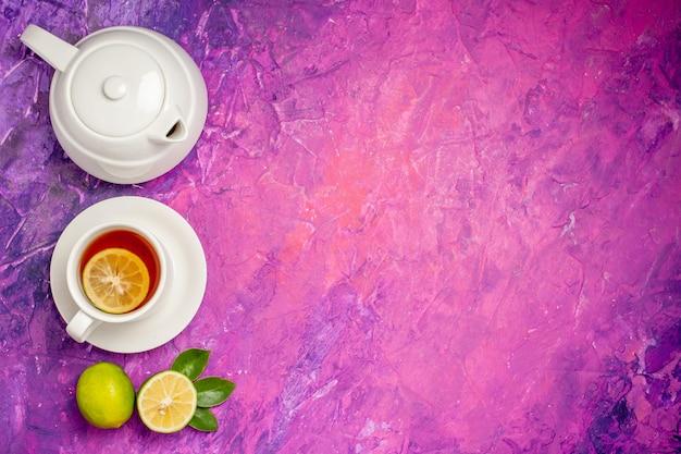 レモン入りティーティーポットの横にあるレモン入りティーとピンクパープルのテーブルの左側にあるライム