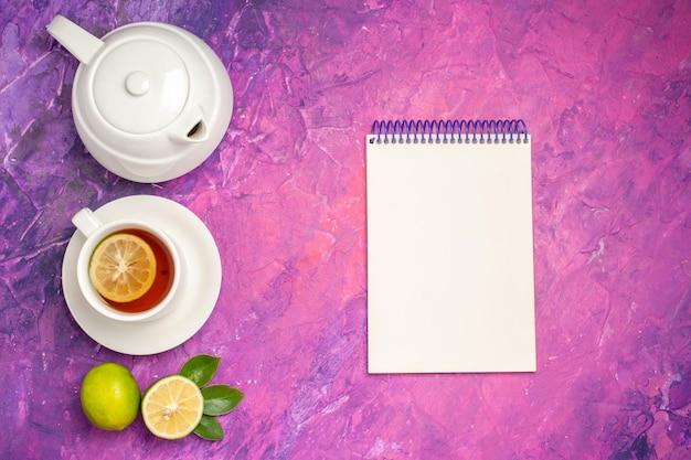 레몬 차 주전자 공책 옆에 레몬 차 한 잔과 분홍색 보라색 테이블에 라임