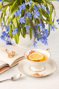 レモンとテーブルの上の青いサクラソウの花束とお茶
