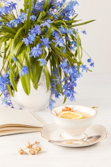 Tea with lemon and bouquet of  blue primroses on the table