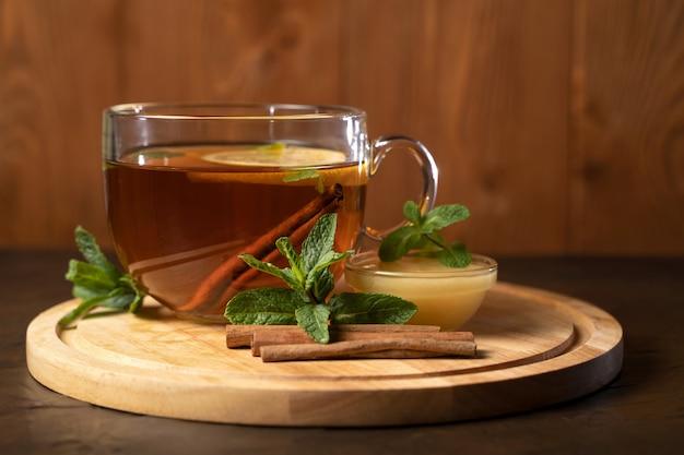 Tea with lemon and cinnamon on wooden board