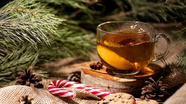 Tea with lemon, next to cookies and lollipop on sackcloth and branches of a christmas tree and cones.
