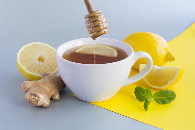 灰色の黄色の背景に白いカップにレモン、蜂蜜、生姜のお茶。閉じる。