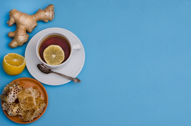 Tea with lemon, honey and ginger root on a blue background with copy space, top view. prevention of colds, to enhance immunity in the autumn and winter.