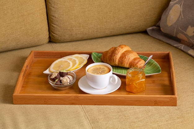 Tea with lemon, jam, croissant and sweets on a wooden tray standing on the sofa