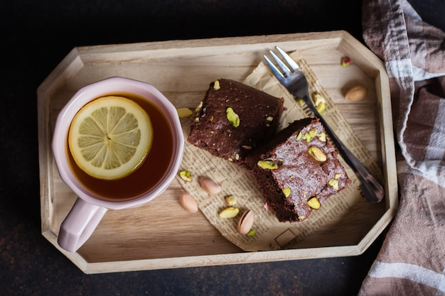 Tea with lemon and mint leaf with homemade biscuit brownie with pistachios for breakfast