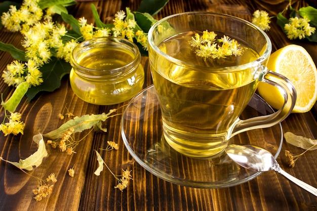 茶色の木製の背景にリンデン、蜂蜜、レモンとお茶