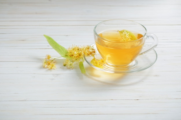 白い木製の背景にリンデンとお茶