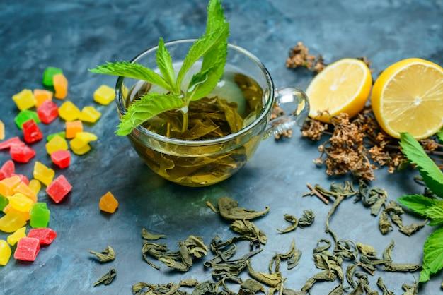 Чай с мятой, сушеные травы, лимон, сладости в чашку на синей поверхности, высокий угол обзора.