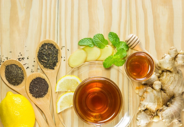Tea with mint honey ginger and lemon on wood background.