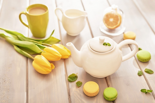 Tea with mint and lemon on the table with macaroons and yellow tulips