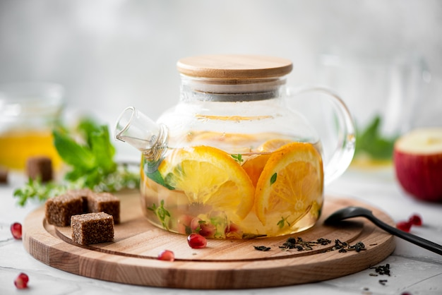 Tea with orange and apple in a glass teapot