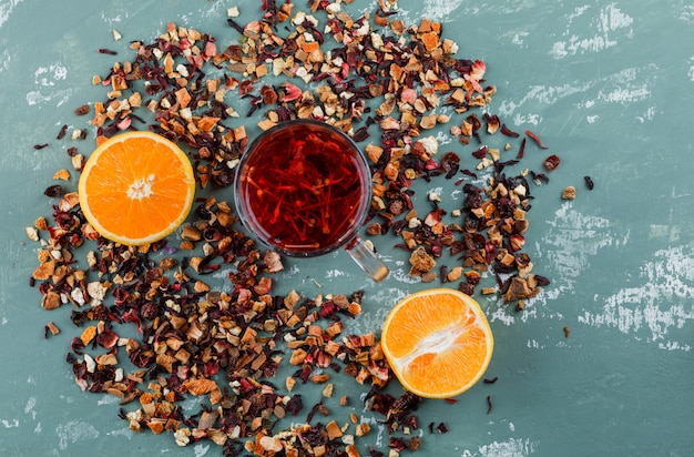 Чай с апельсином, смешанные сушеные травы в чашке на поверхности штукатурки, вид сверху