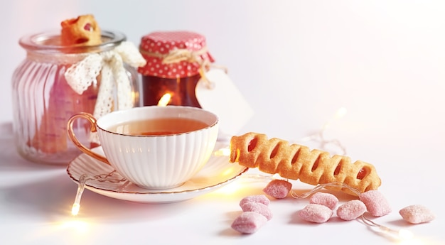 Tea with pastries for breakfast. sweets and pastries with nuts for tea on white background. a coffee cup and patties.