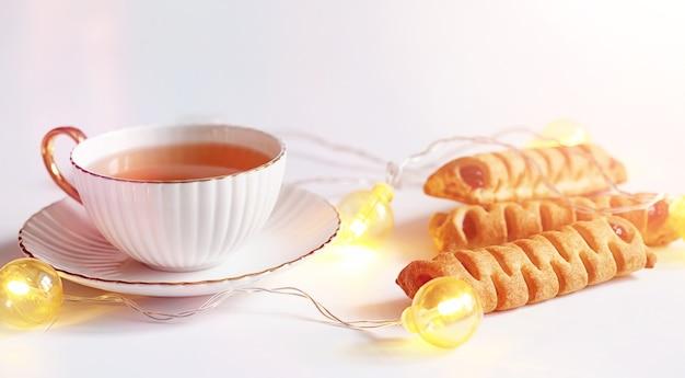 아침 식사로 패스트리와 함께 차. 흰색 바탕에 차를 위한 견과류와 과자와 패스트리. 커피잔과 패티.