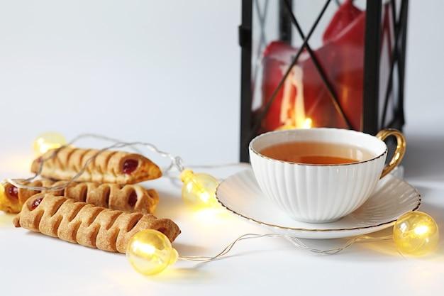 朝食にペストリーとお茶。白い背景の上のお茶のナッツとお菓子やペストリー。コーヒーカップとパテ。