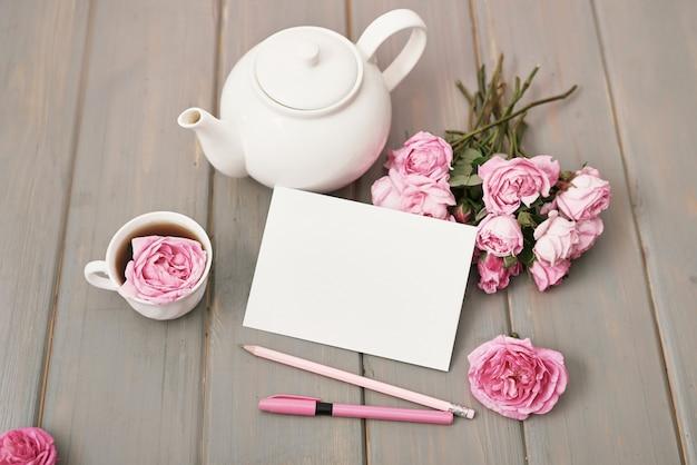 灰色の木製テーブル、コピー領域にピンクのバラとお茶。グリーティングカード