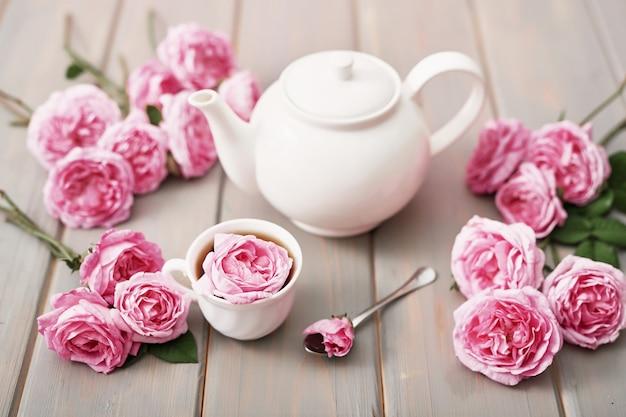 灰色の木製テーブル、コピー領域にピンクのバラとお茶。