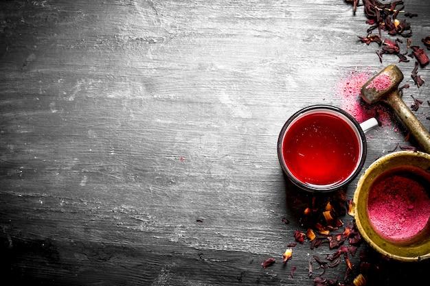 Чай с гранатом, измельченный в ступке на черном деревянном столе.