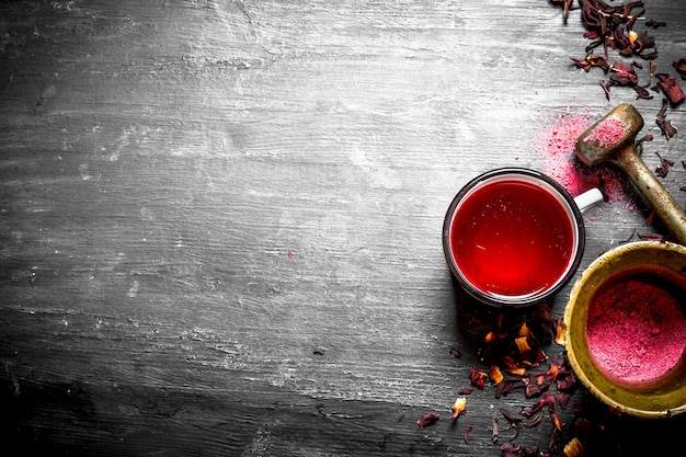 Tea with pomegranate crushed in a mortar on black wooden table.