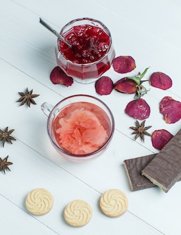 Tea with rose petals, jam, spice, cookies in a cup on wooden table, flat lay.