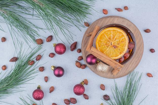 Tè con cinorrodi e palle di natale sulla superficie in marmo.