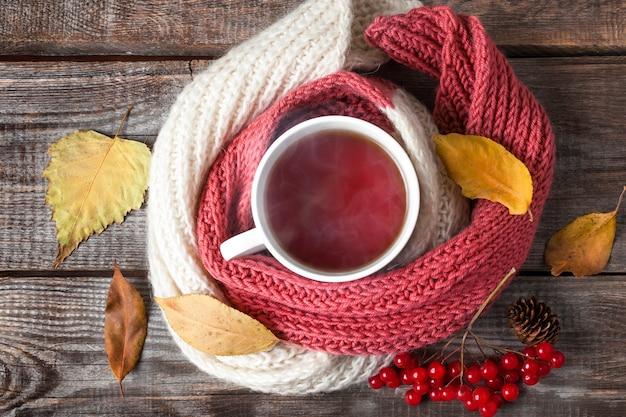 木製の背景にスカーフ、紅葉、赤いベリーとお茶