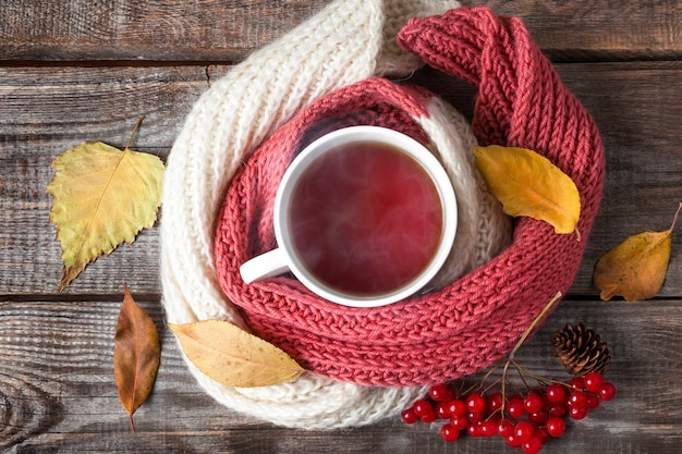 Tea with scarf, autumn leaves and red berries on wooden backgroun