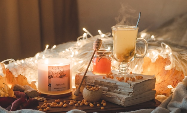 Tea with sea-buckthorn berries and ginger on old books, honey, candle and autumn leaves. the atmosphere of comfort at home. warm cozy home.