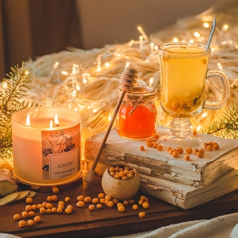 Tea with sea-buckthorn berries and ginger on old books, honey, candle and conifer branches. the atmosphere of comfort at home. warm cozy home.