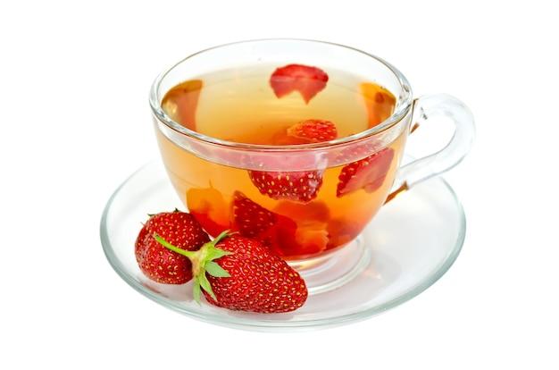 白い背景で隔離のガラスカップにイチゴとお茶