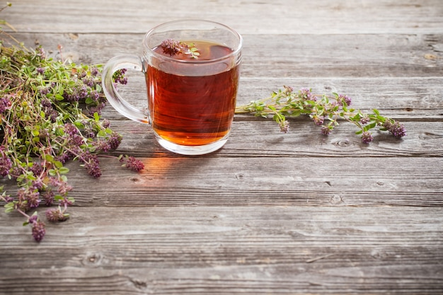 古い木製の背景にタイムとお茶