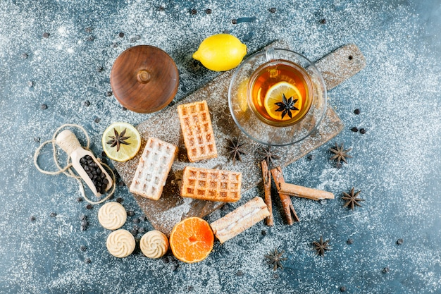 Tea with waffle, biscuit, spices, choco chips, orange in a cup on grungy and cutting board surface, flat lay.