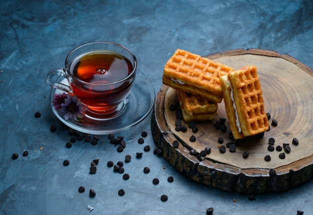 Tea with waffle, chocolate chips, flowers in a cup on blue and wooden board surface, high angle view.