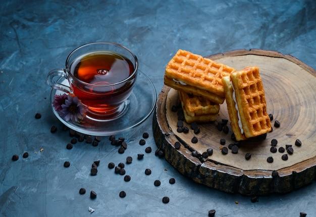Чай с вафлей, шоколадной стружкой, цветами в чашке на поверхности голубой и деревянной доски, высокий угол обзора.