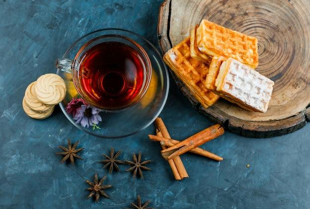 ワッフル、ビスケット、シナモンスティック、カップのスパイスと汚れた青と木の板の表面、平らなお茶。
