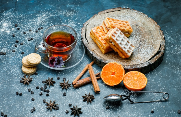 Tea with waffles, biscuits, spices, choco chips, strainer, orange in a cup on blue and wooden board surface, high angle view.