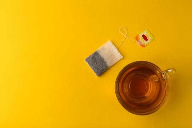黄色の背景にティーバッグとお茶のカップ。