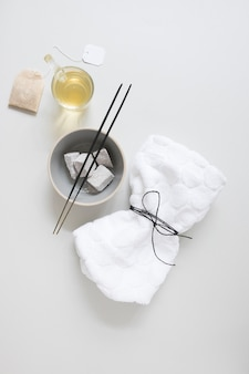 Teabag; oil; pumice stone; incense stick and tied napkin on white surface