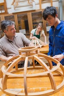 フレームに取り組んでいる木工クラスの教師と学生