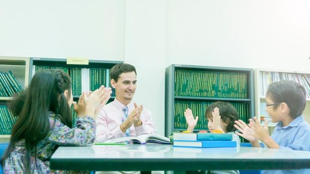 教師と学生の学習のグループと本棚付きのカラーブックで話す