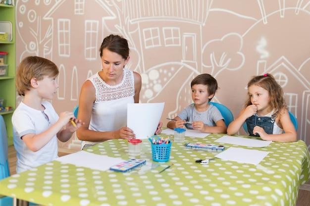 先生とテーブルで子供たち