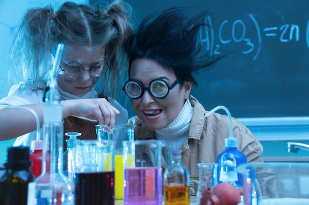 화학 물질을 혼합 화학 수업 중 교사와 어린 소녀
