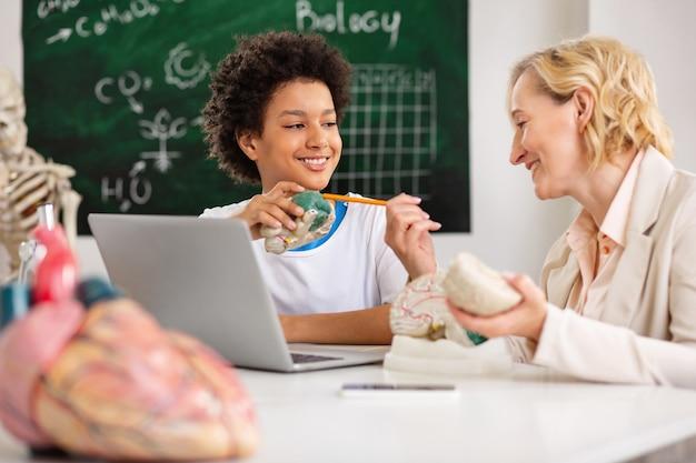 교사와 학생. 그에게 자료를 설명하는 동안 그녀의 학생과 이야기하는 좋은 쾌활한 여자