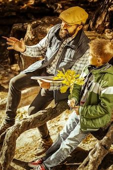 좋은 날에 수업을 갖는 숲의 나무 뿌리 사이에 앉아 교사와 학생