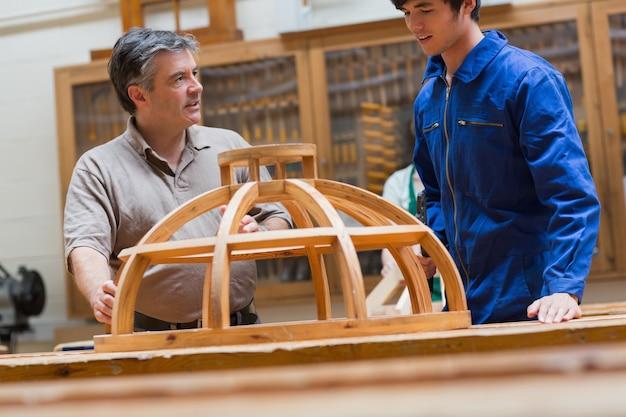 木製のフレームを話す教師と学生