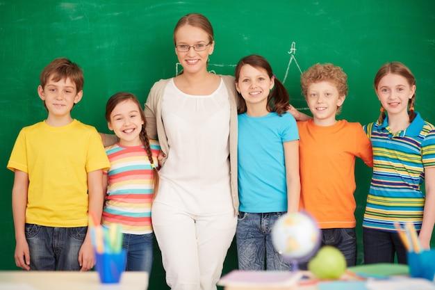 Учителя и студенты, стоя перед доске