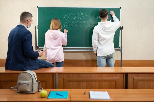 Учитель и ученики в защитных масках возле доски во время карантина