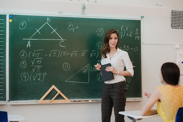 Teacher answering pupils question in classroom