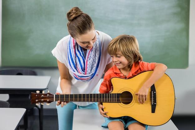 先生が少年がギターを弾くのを手伝って